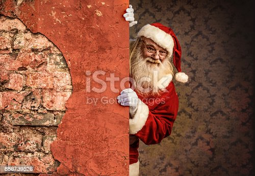 istock Santa Claus pointing on brick wall 886739526