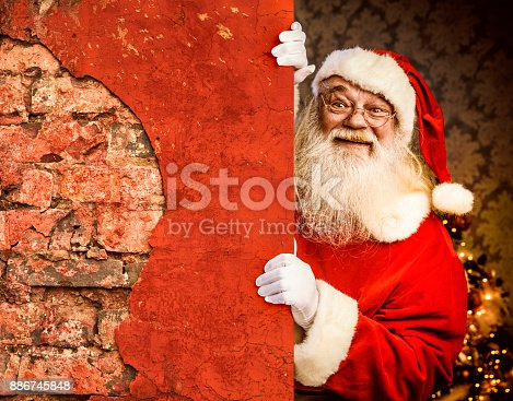 istock Santa Claus pointing on brick wall 886745848