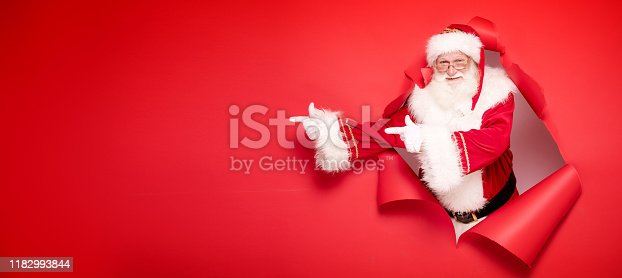 istock Santa Claus pointing on red empty background. 1182993844