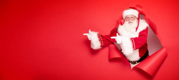 Santa Claus pointing on red empty background. Santa Claus , the real one, comes out of the red studio background pointing on empty copy space. Christmas time. only senior men stock pictures, royalty-free photos & images