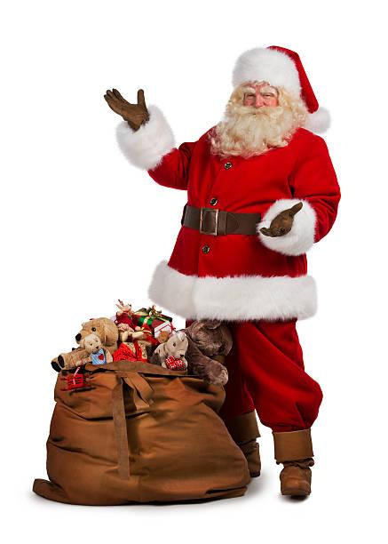 santa claus posing near a bag full of gifts stock photo - Santa Claus Gifts