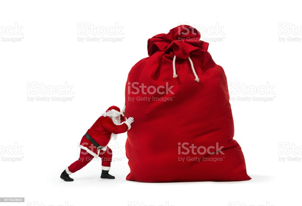 Santa Claus pushing huge bag of christmas gifts - foto stock