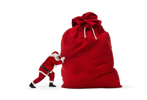 santa claus pushing huge bag of christmas gifts - babbo natale foto e immagini stock