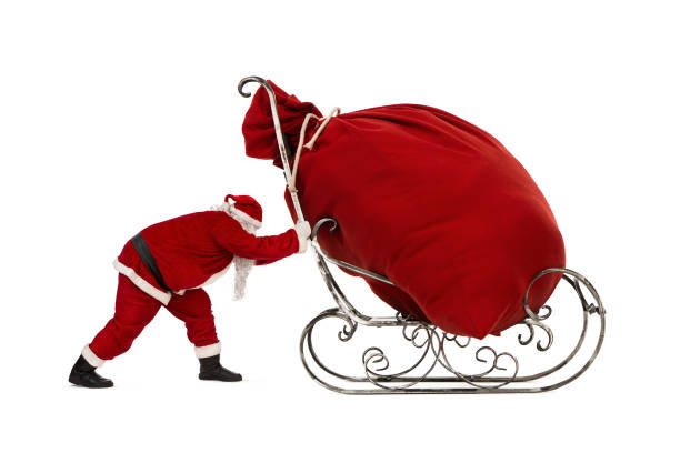 Santa Claus pushing sleigh with huge bag of christmas gifts on it Close up of Santa Claus pushing sleigh with huge bag of christmas gifts on it, isoolated on white background sleigh stock pictures, royalty-free photos & images