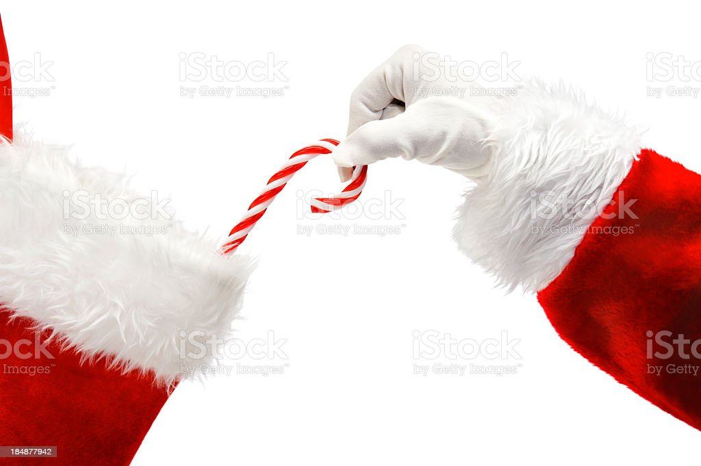 Santa Claus putting a candy cane in a stocking stock photo