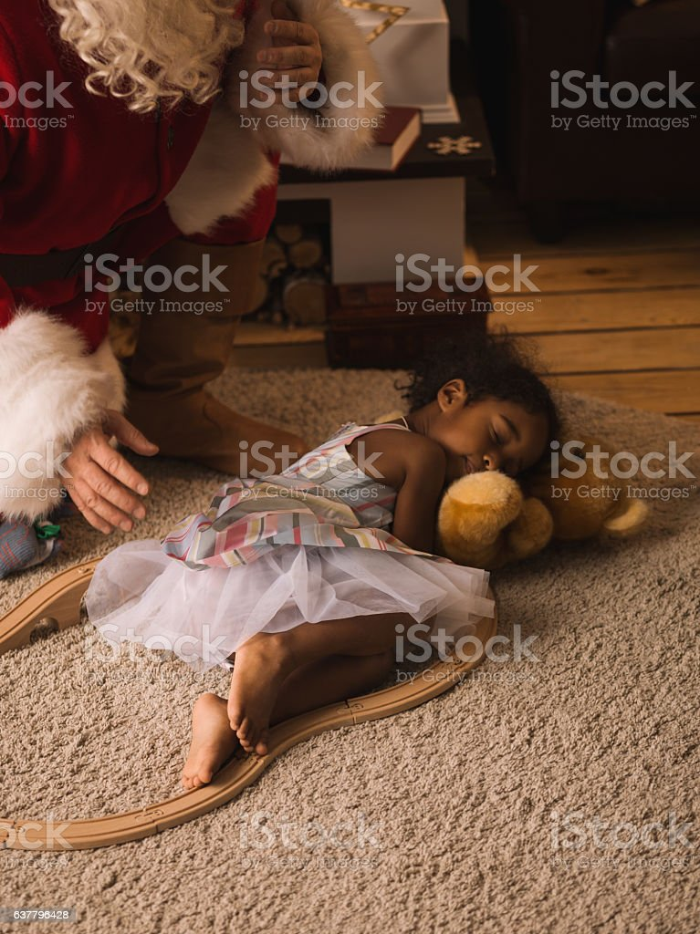 Santa Claus putting down sleepy child at home stock photo