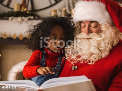 istock Santa Claus reading a book with child near Christmas tree 636864638