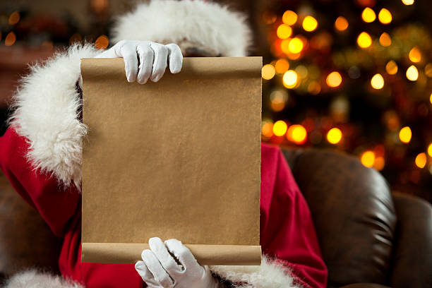 Santa Claus reading a wish list at home. stock photo