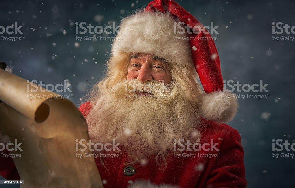Santa Claus reading Christmas letter stock photo