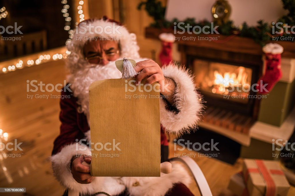Santa Claus reading a wish list during New Year\'s Eve at home. Focus...