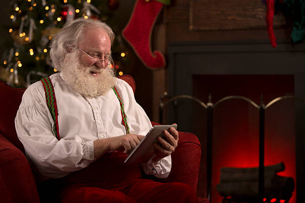 santa claus liest seine ungezogen und brav-liste auf tablet pc - weihnachtsprogramm stock-fotos und bilder