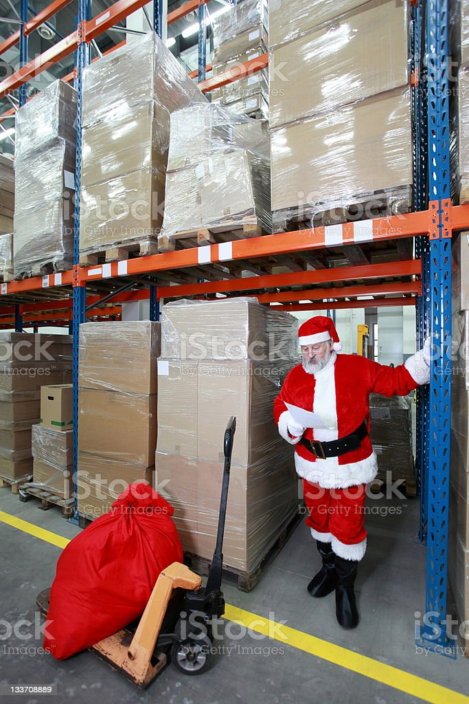 Santa claus reading wishing list of presents in storehouse royalty-free stock photo
