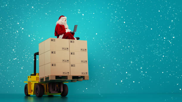 Santa Claus reads from laptop presents request and boxes to delivery stock photo