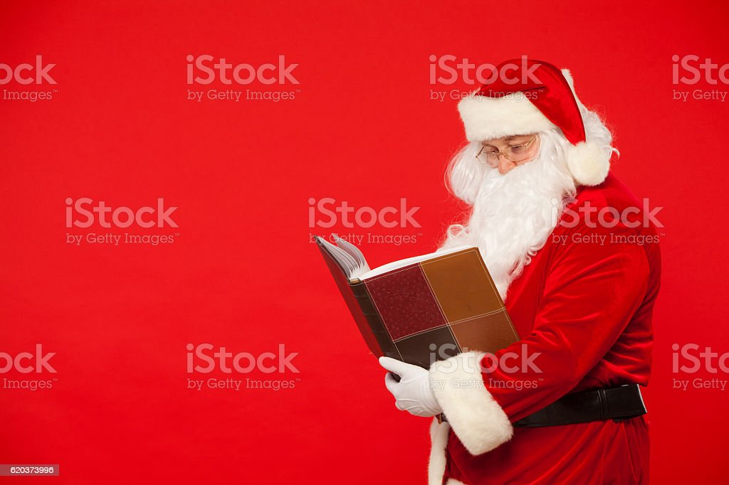 Santa Claus reads old book, on a red background. Christmas foto de stock royalty-free