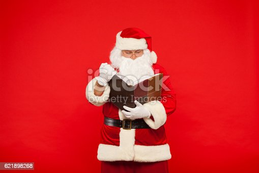 621898406istockphoto Santa Claus reads old book, on a red background. Christmas 621898268