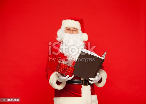 621898406istockphoto Santa Claus reads old book, on a red background. Christmas 621898406
