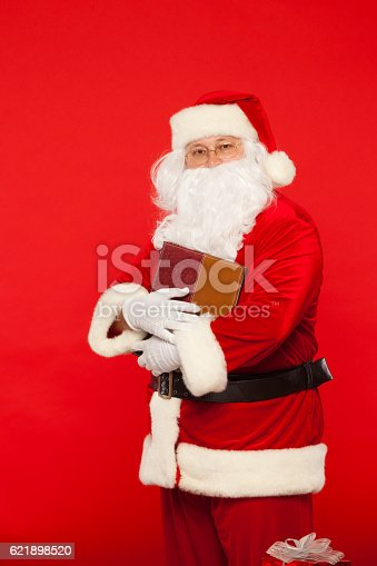 621898406istockphoto Santa Claus reads old book, on a red background. Christmas 621898520