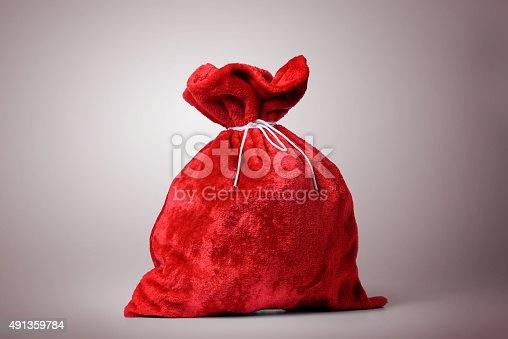 istock Santa Claus red bag full on background 491359784