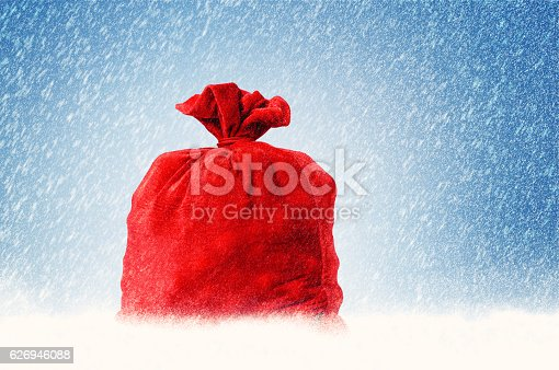 istock Santa Claus red bag full, on snow background. 626946088