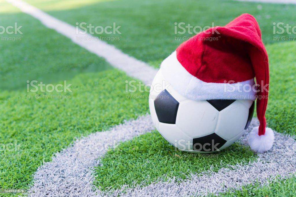 Santa Claus roten Hut auf Fußball am grünen Rasen – Foto
