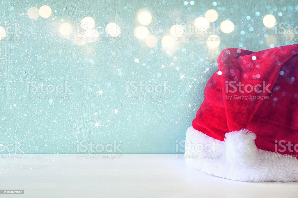 Santa claus red hat on wooden table. Glitter overlay stock photo