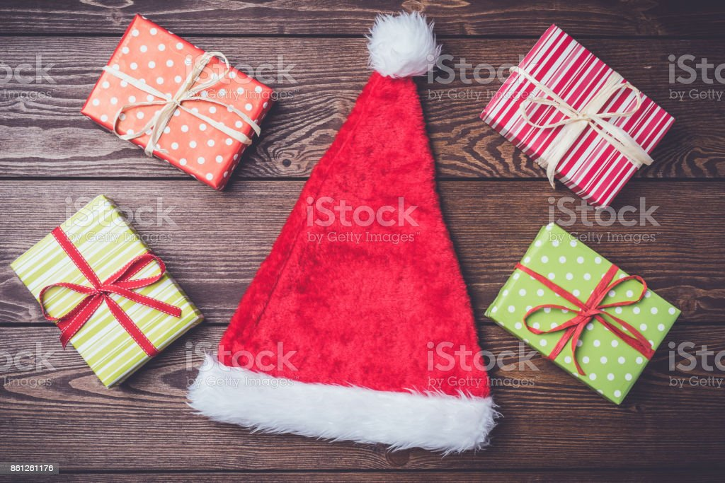 Santa Claus red hat with colorful gift boxes. Close up