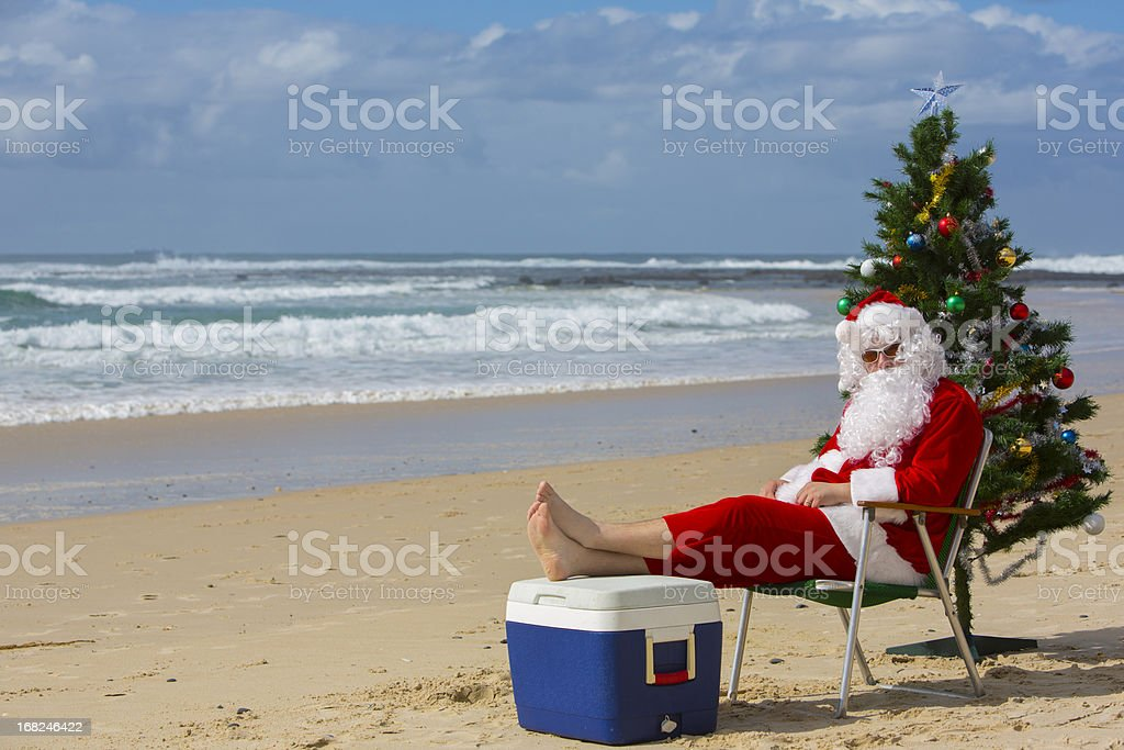 santa claus relaxing at the beach with a christmas tree royalty free stock photo - Christmas At The Beach