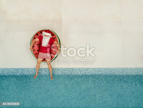 istock Santa Claus relaxing at the pool 842805908