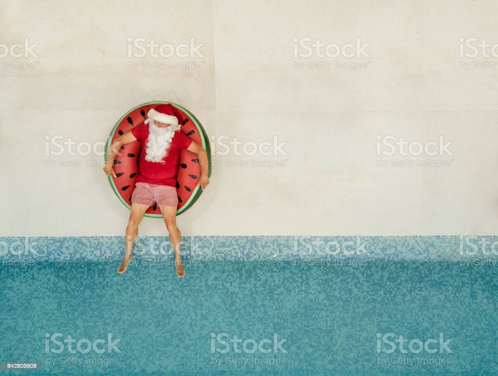Santa Claus relaxing at the pool stock photo
