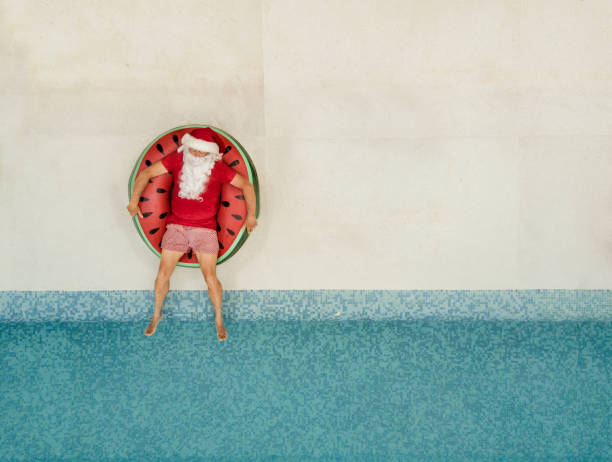 santa claus relaxing at the pool - babbo natale foto e immagini stock