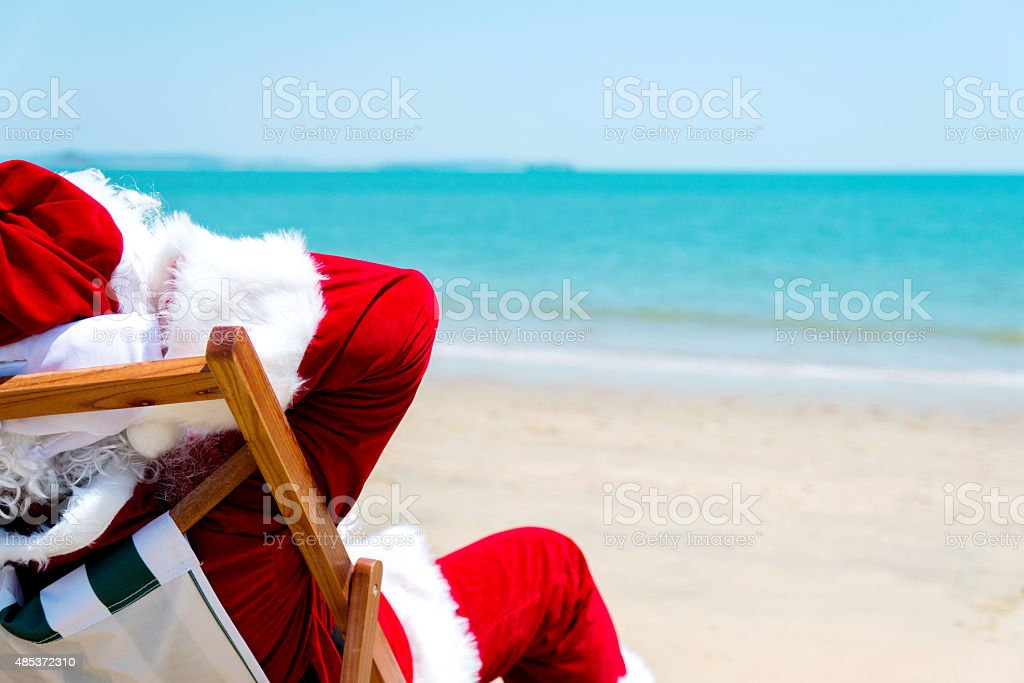 Santa claus relaxing on beach stock photo