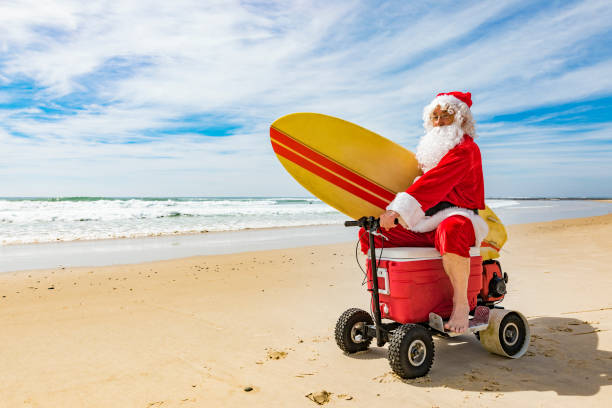 Santa Claus Riding a Motorised Esky Cooler on the Beach stock photo