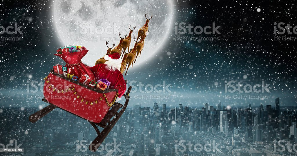 Santa Claus riding on sled against balcony overlooking city stock photo