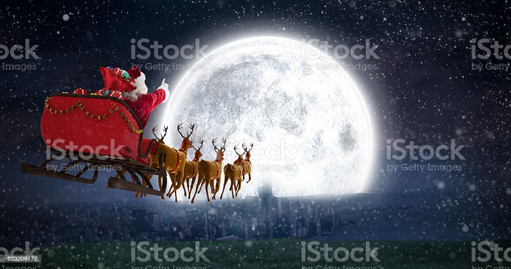 Santa Claus riding on sleigh against bright moon stock photo