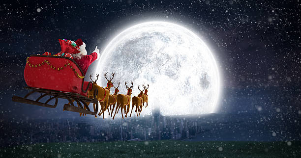 Santa Claus riding on sleigh against bright moon Santa Claus riding on sleigh with gift box against bright moon over city sled stock pictures, royalty-free photos & images