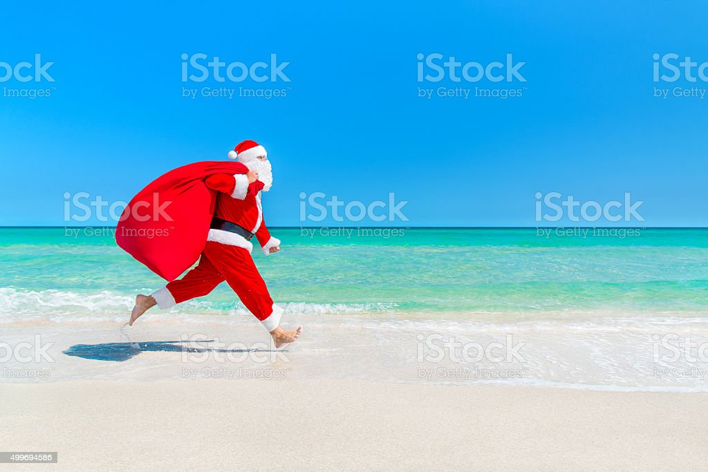Santa Claus running along beach with sack full of gifts stock photo