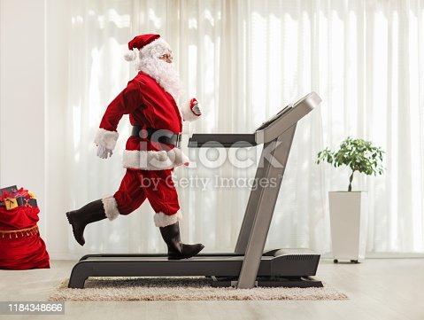 Full length profile shot of Santa Claus running on a treadmill at home