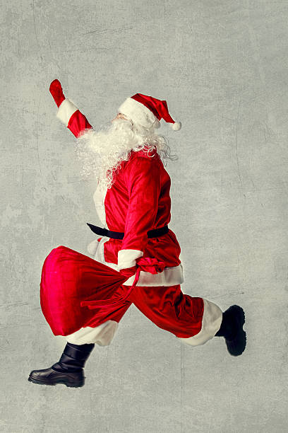 santa claus running with a bag of gifts. - schnelles weihnachtsessen stock-fotos und bilder