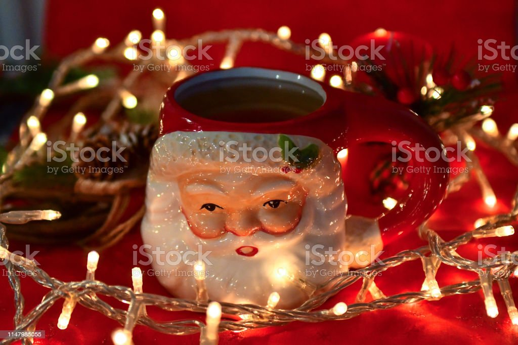 Santa Claus shaped tea mug with tea inside and Christmas lights and...