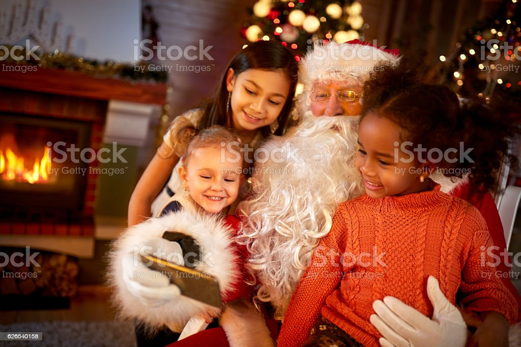 Santa Claus sharing smart phone with children - foto stock