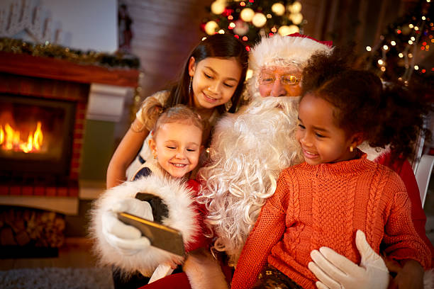 santa claus sharing smart phone with children - pere noel photos et images de collection