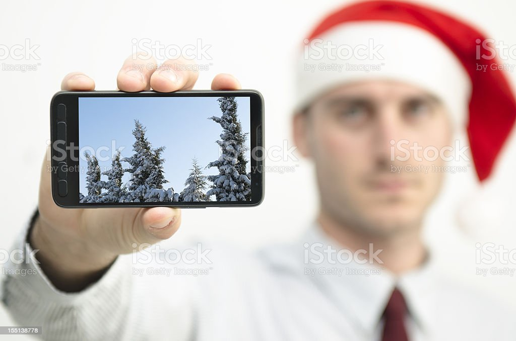 Santa Claus showing contemporary smart phone with winter image royalty-free stock photo