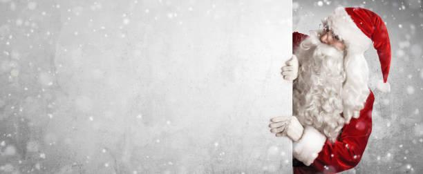 weihnachtsmann zeigt etwas an einer weißen wand - santa stock-fotos und bilder