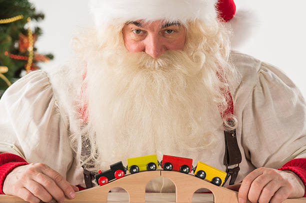 santa claus sitzen und spielen mit spielzeug-eisenbahn wie zu hause fühlen - festzugskleidung stock-fotos und bilder