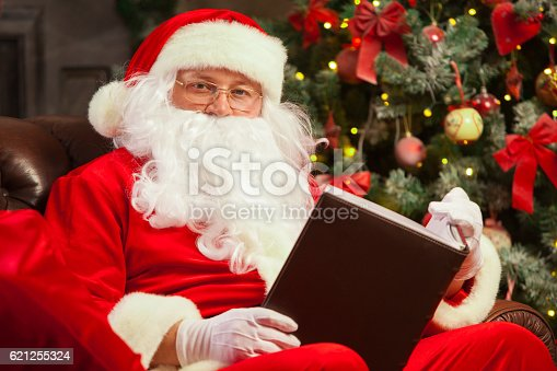 621898406istockphoto Santa Claus sitting at his home in a comfortable chair 621255324