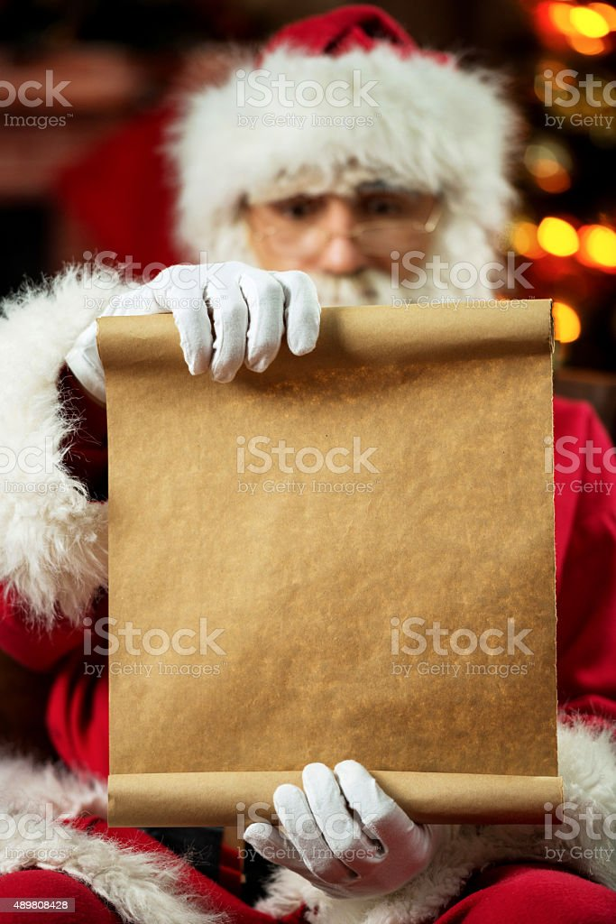 Santa Claus sitting at home and reading a list. stock photo