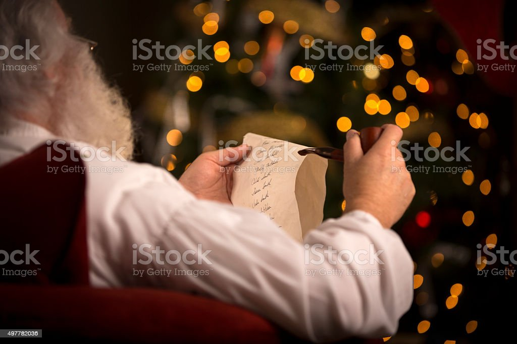 Santa Claus sitting at home, holding a pipe stock photo