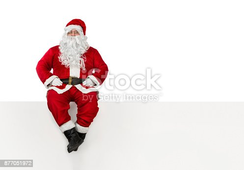 istock Santa Claus sitting at the edge of a blank banner 877051972