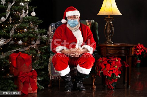 horizontal photograph of Santa Claus Sitting in a Chair Wearing a Surgical Mask and Looking Towards the Camera
