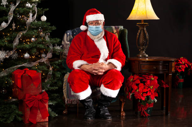 santa claus sitting in a chair wearing a surgical mask and looking towards the camera - santa claus imagens e fotografias de stock